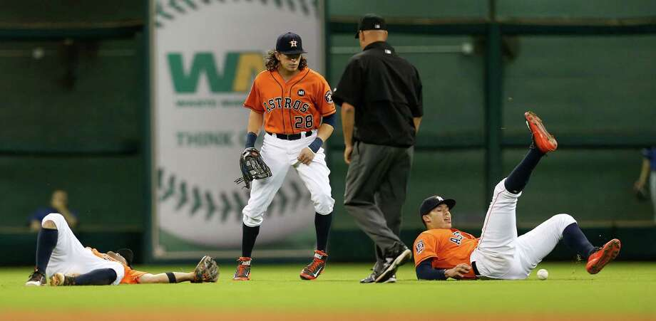Houston Astros second baseman Jose Altuve (27) and shortstop Carlos Correa (1) collided going for a double hit by Texas Rangers shortstop Elvis Andrus (1) during the seventh inning of an MLB game at Minute Maid Park on Friday, Sept. 25, 2015. ( Karen Warren / Houston Chronicle ) Photo: Karen Warren, Staff / © 2015 Houston Chronicle