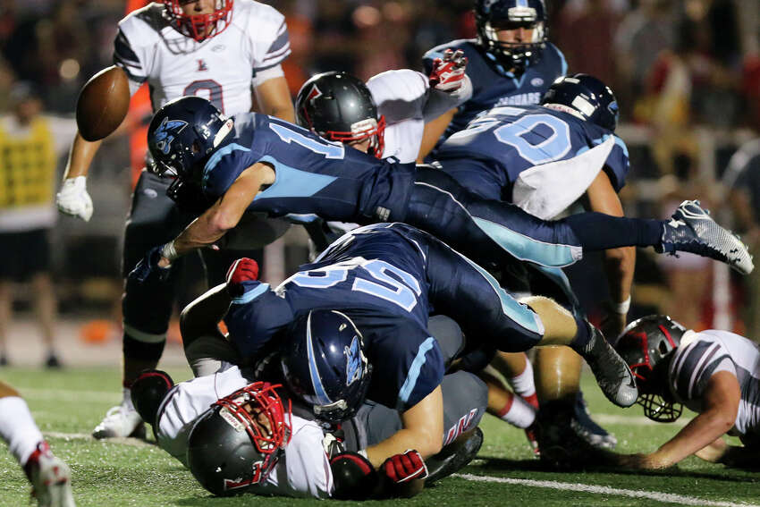 Johnson's Dylan Pouncey (center) loses the ball as he dives for extra yardage during the first half of their District 26-6A game with Lee at Comalander Stadium on Friday, Sept. 25, 2015. MARVIN PFEIFFER/ mpfeiffer@express-news.net