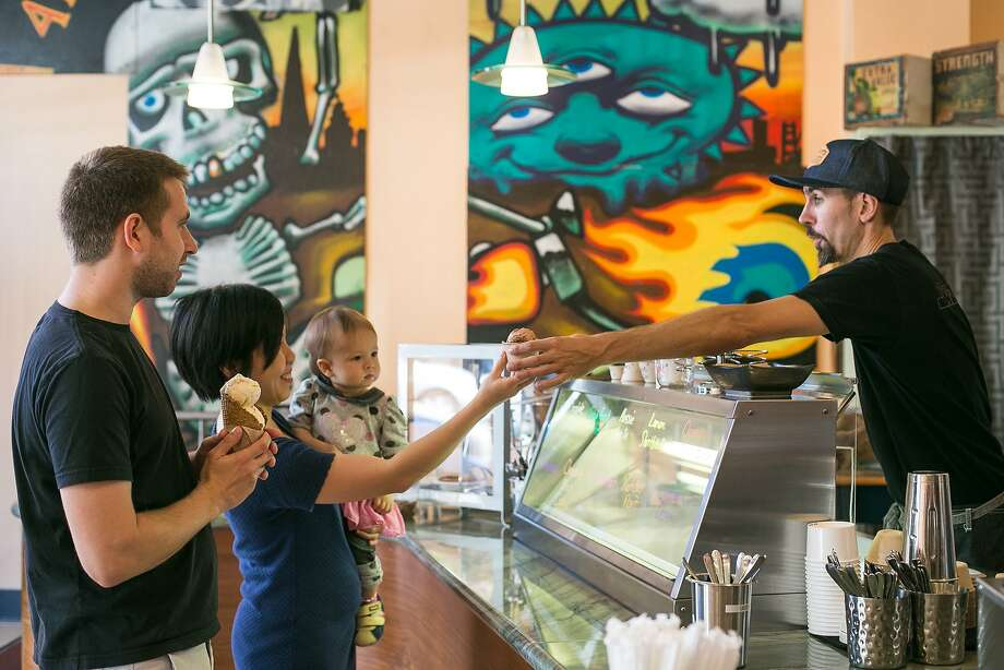 Jeffery Mann, Shakedown's co-owner, hands a scoop of ice cream to Faith Donal inside the birghtly colored ice cream shop. Photo: Jen Fedrizzi, Special To The Chronicle