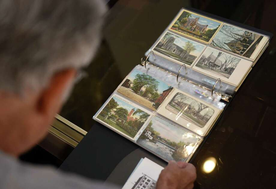 Stamford native Lester Sharlac pages through his collection of historic Stamford postcards, ranging in date from the 1900s up until nearly present day, at his home in Stamford, Conn. Thursday, Aug. 13, 2015. Photo: Tyler Sizemore / Hearst Connecticut Media / Greenwich Time