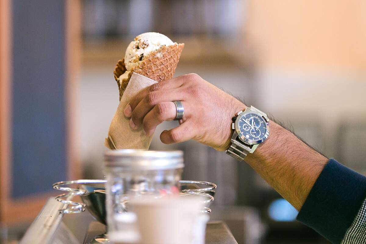 A customer pulls his ice cream cone from the holder in the Tenderloin's new ice cream shop, Shakedown.