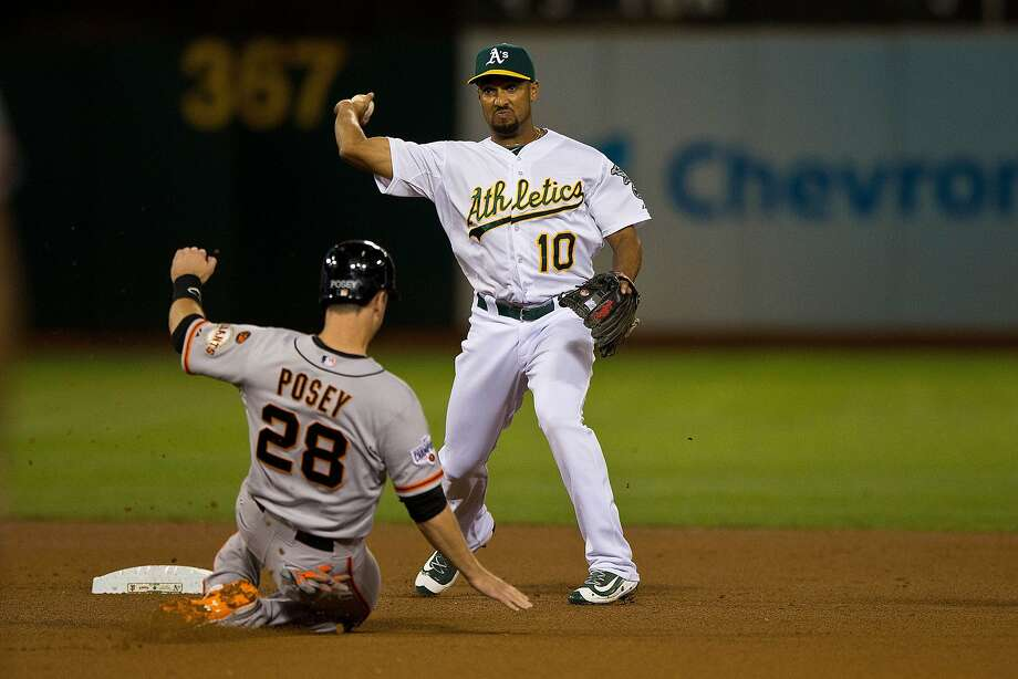 A's shortstop Marcus Semien completes a double play over Buster Posey of the Giants Giants during the fourth inning at the Coliseum on September 25, 2015. (Photo by Jason O. Watson/Getty Images) Photo: Jason O. Watson, Getty Images