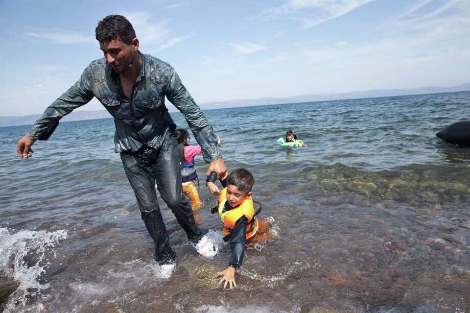 A Syrian father helps his child as they arrive  from Turkey to the shores of the Greek island of Lesbos, on an inflatable dinghy, Saturday Sept. 26, 2015. More than 260,000 asylum-seekers have arrived in Greece so far this year, most reaching the country's eastern islands on flimsy rafts or boats from the nearby Turkish coast. Photo: Petros Giannakouris, AP / AP