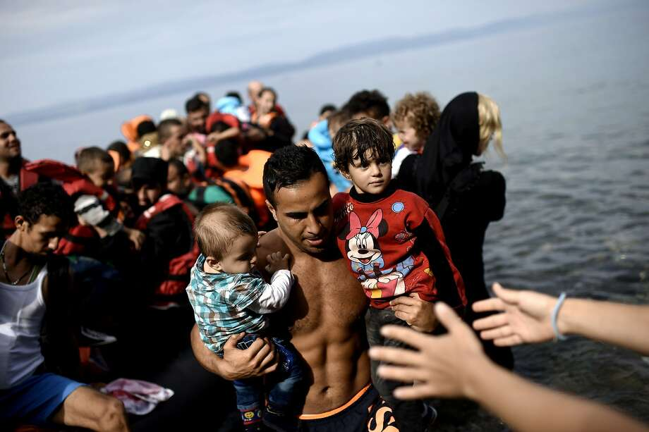 A man carries children as refugees arrive on the Greek island of Lesbos after crossing the Aegean sea from Turkey. Photo: Aris Messinis, AFP / Getty Images