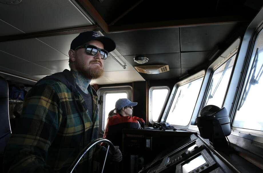 Capt. Chris Eubank (left) and researcher Danielle Lipski survey the ocean aboard the research vessel Fulmar. Photo: Michael Macor, The Chronicle