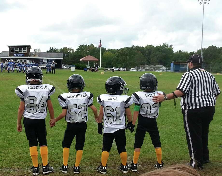 Pop Warner football players #84 Aiden Pollizatto, #52 Nathan Richtmeyer, #61 David Bovia and #33 Jeremiah Casey