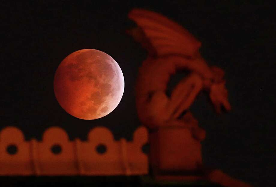 A lunar eclipse appears behind a gargoyle atop the old red Dallas County Courthouse early Wednesday morning, Oct. 8, 2014.  The moon appears orange or red, the result of sunlight scattering off Earth's atmosphere. This is known as the blood moon. (AP Photo/The Dallas Morning News, Tom Fox)  MANDATORY CREDIT; MAGS OUT; TV OUT; INTERNET USE BY AP MEMBERS ONLY; NO SALES Photo: Tom Fox / Associated Press / The Dallas Morning News