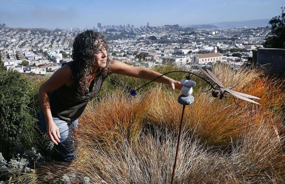 Mindy Linetzky adjusts a rotating dragonfly sculpture in her backyard garden which was included in this year's Portola Garden Tour in San Francisco, Calif. on Saturday, Sept. 26, 2015. Photo: Paul Chinn, The Chronicle