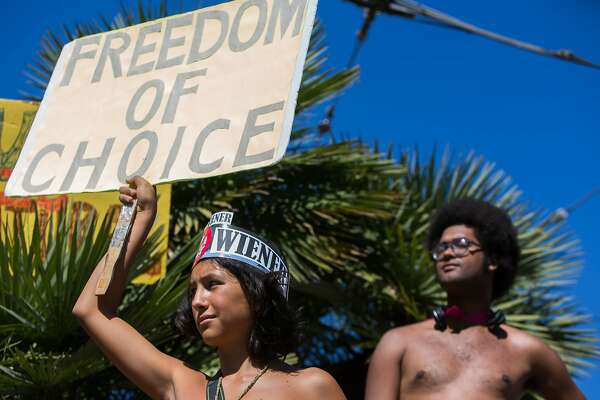 From left, Inti Gonzalez, 14 Gamely Anumu attend a nudist rally on Saturday, Sept. 26, 2015 in San Francisco, Calif.  Nudists hold a nude-in at Jane Warner Plaza in the Castro after a San Francisco judge ruled the city had to issue them a permit.