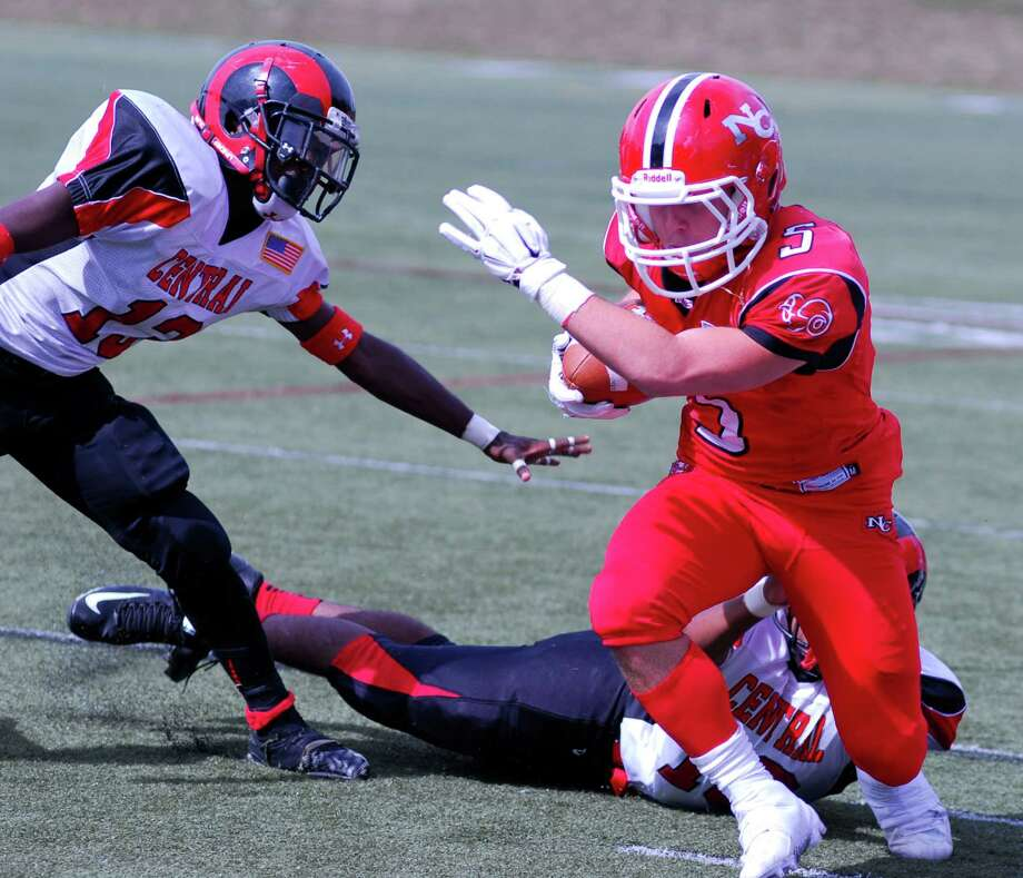 New Canaan's Matt Cognetta, right, breaks a tackle from a Bridgeport Central player during a football game at New Canaan High School on Saturday, Sept. 26 2015. Photo: Ryan Lacey/Staff Photo / Westport News Contributed