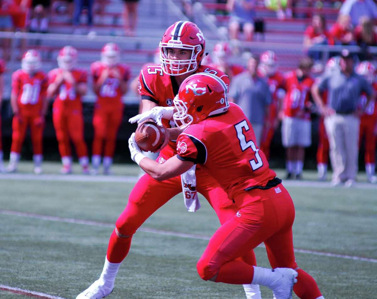 New Canaan quarterback Michael Collins, left hands the ball off to Matt Cognetta a football game against Bridgeport Central at New Canaan High School on Saturday, Sept. 26 2015.