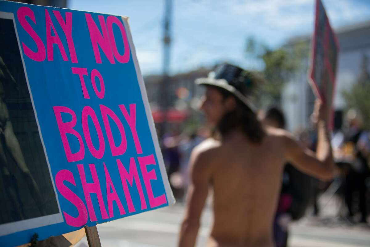 Ryan Campbell holds a sign at a nudist rally on Saturday, Sept. 26, 2015 in San Francisco, Calif. Nudists hold a nude-in at Jane Warner Plaza in the Castro after a San Francisco judge ruled the city had to issue them a permit.