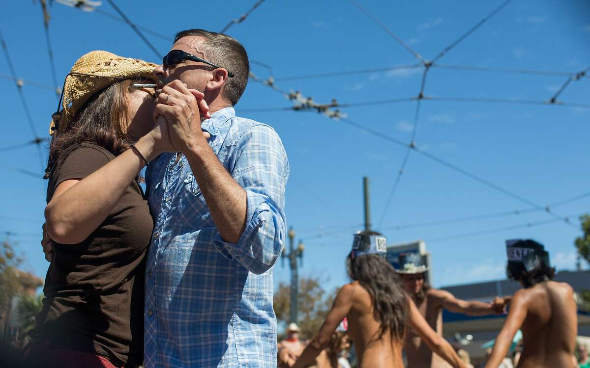 Kirsten Hall and Christopher Friday dance to a live swing band while a group of nudist join in on Saturday, Sept. 26, 2015 in San Francisco, Calif. Nudists hold a nude-in at Jane Warner Plaza in the Castro after a San Francisco judge ruled the city had to issue them a permit.