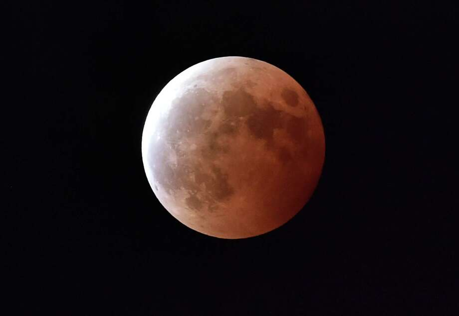 "(FILES) -- This file photo taken on October 8, 2014 shows a lunar eclipse as seen from Tokyo. For the first time in decades, skygazers are in for the double spectacle on September 28, 2015 of a swollen ""supermoon"" bathed in the blood-red light of a total eclipse. AFP PHOTO / Yoshikazu TSUNO