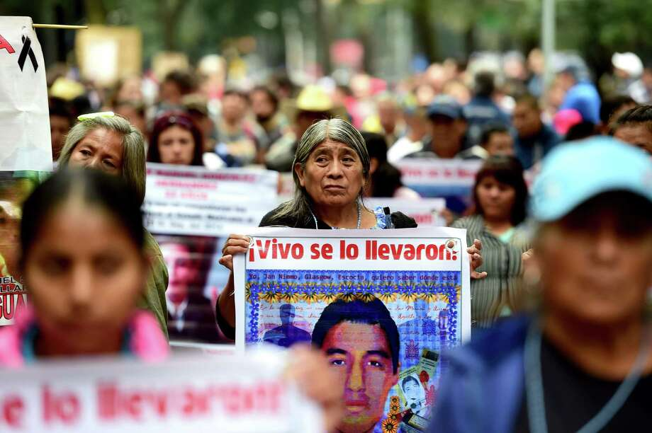 Students and relatives of the 43 missing students from Ayotzinapa take part during a protest in Mexico City to commemorate the first anniversary of their disappearance. Photo: Ronaldo Schemidt /Getty Images / AFP