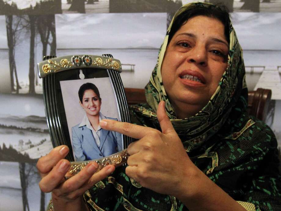 Sarwari Begum of Pakistan shows a picture of her daughter, Bushra Khalique, 27, who is reportedly missing after a crush during the hajj pilgrimage.  Photo: Fareed Khan, STR / AP