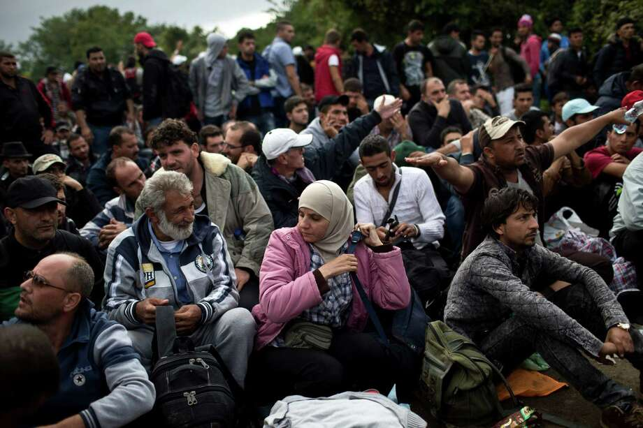 People wait to clear a police line as they entered into Croatia from Serbia, in Babska, Croatia, Friday, Sept. 25, 2015. Croatia lifted its blockade of the border with Serbia on Friday, as southeastern Europe's squabbling governments took steps to ease tensions that had been rising in the region because of the surge of asylum seekers seeking refuge in the rest of Europe. (AP Photo/Marko Drobnjakovic) Photo: Marko Drobnjakovic, STR / AP