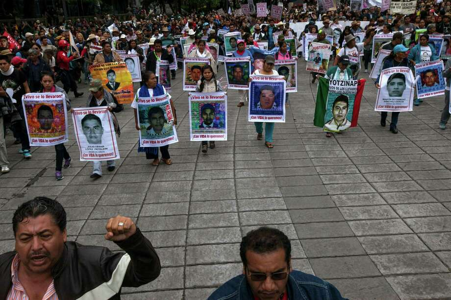 Relatives of 43 missing college students, who were allegedly taken by police and then handed over to a criminal gang, marked the one-year anniversary of their disappearance with a march Saturday in Mexico City.  Photo: Marco Ugarte, STF / AP