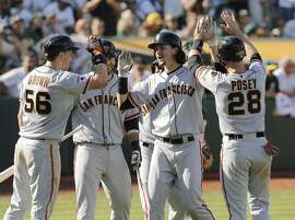 Trevor Brown, Brandon Crawford, Jarrett Parker, Marlon Byrd, (behind Parker) and Buster Posey greet Parker at home after his grand slam in the eighth inning to put the Giants' up 14-10, as the San Francisco Giants take on the Oakland Athletics at O.co Coliseum, Calif. on Sat. September 26, 2015.