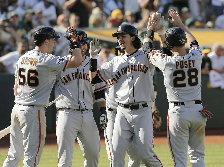 Trevor Brown, Brandon Crawford, Jarrett Parker, Marlon Byrd, (behind Parker) and Buster Posey greet Parker at home after his grand slam in the eighth inning to put the Giants' up 14-10, as the San Francisco Giants take on the Oakland Athletics at O.co Coliseum, Calif. on Sat. September 26, 2015. Photo: Michael Macor, The Chronicle