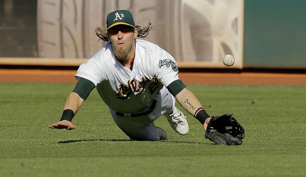 A's Josh Reddick dives for a Buster Posey hit that gets by him for a double in the eighth inning, as the San Francisco Giants went on to beat the Oakland Athletics 14-10 at O.co Coliseum, Calif. on Sat. September 26, 2015.