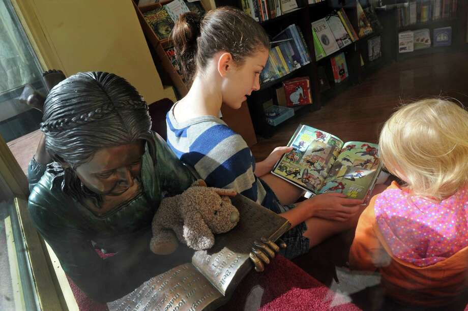 Thirteen-year-old Kelly O'Neil reads to 3-year-old Ellie, no last name given, at Market Block Books on Saturday Sept. 26, 2015 in Troy, N.Y.  (Michael P. Farrell/Times Union) Photo: Michael P. Farrell