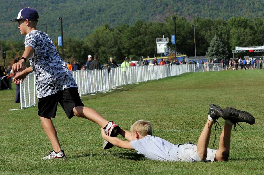 Joey Bozzo, 14, of Ballston Spa, left, drags his friend Troy Gottmann, 10, of Malta across the final stretch of the Queensbury Invitational cross country meet on Saturday, Sept. 26, 2015, at Queensbury High in Queensbury, N.Y. (Cindy Schultz / Times Union) Photo: Cindy Schultz / 00033515A