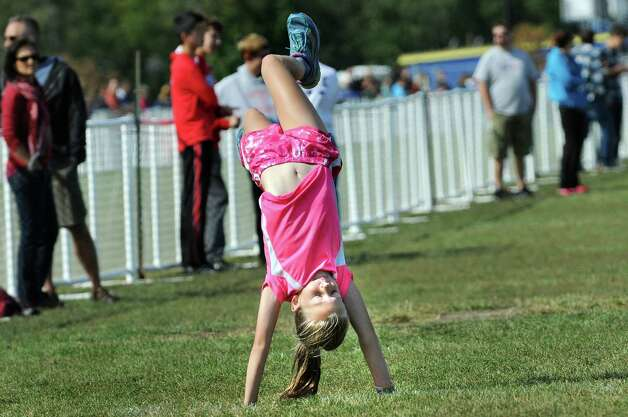 Ryle Davis, 9, of Bethlehem, center, does a handstand while attending the Queensbury Invitational cross country meet on Saturday, Sept. 26, 2015, at Queensbury High in Queensbury, N.Y. (Cindy Schultz / Times Union) Photo: Cindy Schultz / 00033515A
