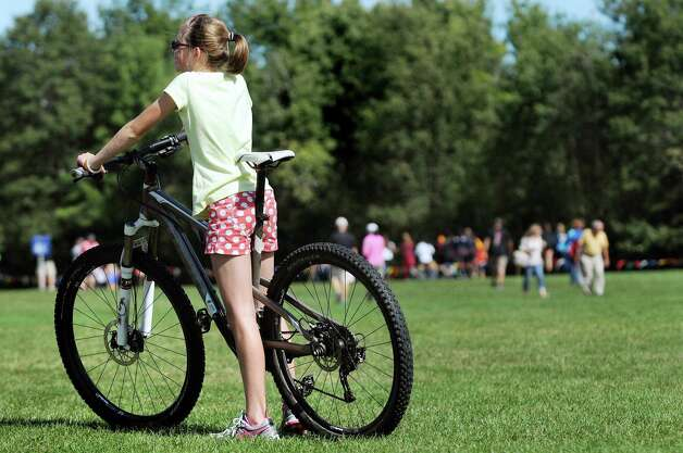 Josie Smith, 12, of Williamstown, Mass. relaxes on the bike of her father, Sam Smith, while attending the Queensbury Invitational cross country meet on Saturday, Sept. 26, 2015, at Queensbury High in Queensbury, N.Y. Josie's sister Margo Smith placed 15th overall for Mt. Greylock in the Division 1 girls' race. (Cindy Schultz / Times Union) Photo: Cindy Schultz / 00033515A