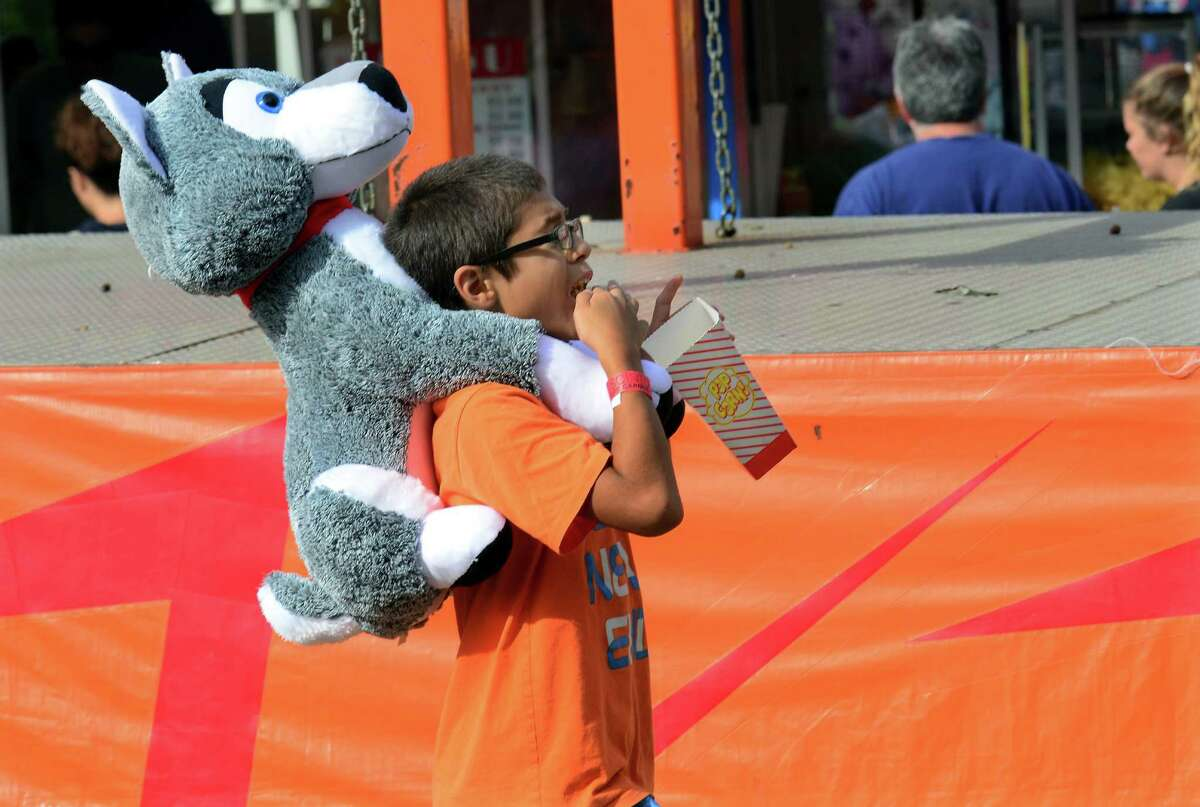 Jamesyn Brothers, 12, of Ansonia, eats popcorn as he carries a stuffed wolf he won at the First Annual R.D. Scinto Family Day Carnival at Scinto Towers in Shelton, Conn. on Saturday Sept. 26, 2015. All money raised will be donated to local charities. Fifty percent will be donated to the Valley United Way and fifty percent will go to the Bridgeport Rescue Mission.