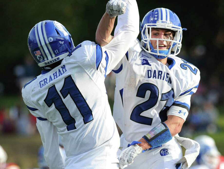 Darien quarterback Tim Graham (#11) left, high-fives Darien running back Shelby Grant (#21) after Grant scored on a 3rd quarter run during the high  school football game between Greenwich High School and Darien High School at Greenwich, Conn., Saturday, Sept. 26, 2015. Darien defeated Greenwich, 51-28. Photo: Bob Luckey Jr. / Hearst Connecticut Media / Greenwich Time