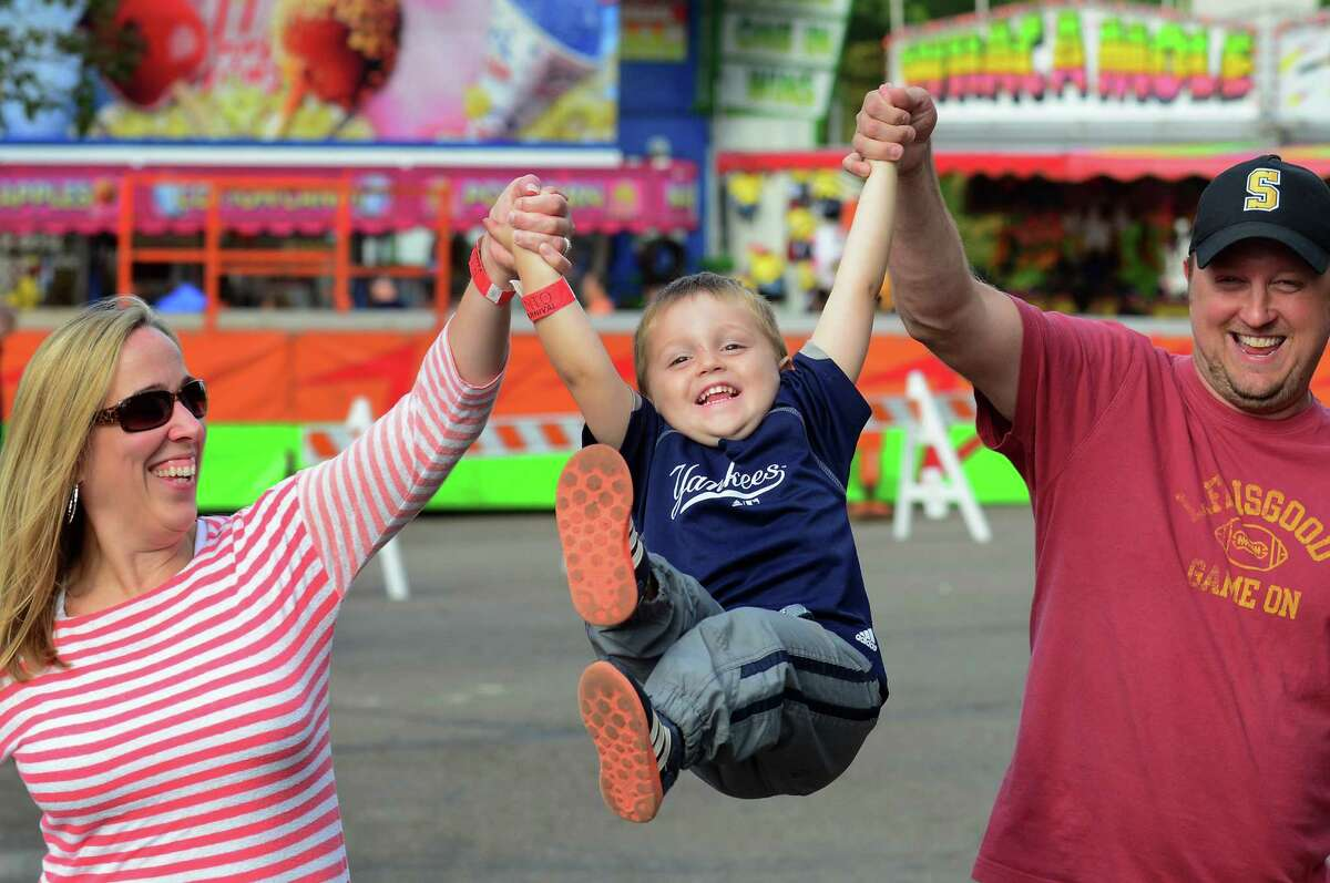 Cori and Russ Duda, of Shelton, lift their son Ryan, 3, into the air as they attend the First Annual R.D. Scinto Family Day Carnival at Scinto Towers in Shelton, Conn. on Saturday Sept. 26, 2015. All money raised will be donated to local charities. Fifty percent will be donated to the Valley United Way and fifty percent will go to the Bridgeport Rescue Mission.