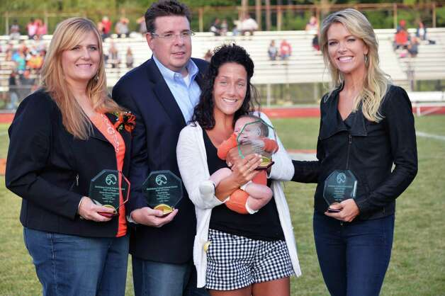 Four BCS alumni recognized for their contributions in sports, journalism, business and health care, from left, Karen Bruni-Fitzgerald, Neal Brady, Chris Quatraro and infant son George, accepting for her husband Matt Quatraro and Megyn Kelly during a Hall of Fame induction ceremony at Bethlehem Central High School Saturday Sept. 26, 2015 in Bethlehem, NY.  (John Carl D'Annibale / Times Union) Photo: John Carl D'Annibale / 00033505A