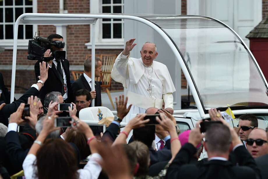 Pope Francis waves to people as his Jeep slowly rolls past Independence Hall in Philadelphia. Photo: Vincenzo Pinto /Getty Images / AFP