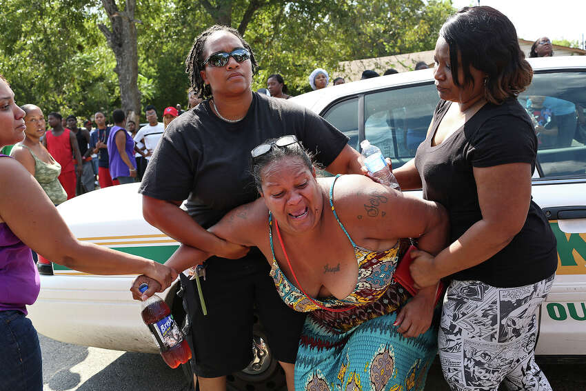 Olivia Fenner, center, the mother of Tru Trusty, 16, grieves at the scene where a young man was shot and killed, who she believes to be Trusty, in San Antonio on Saturday, Sept. 26, 2015. Authorities would not confirm the identity of the victim but friends and family said it was Trusty. Read more: Deadly shooting on East Side claims one, wounds another