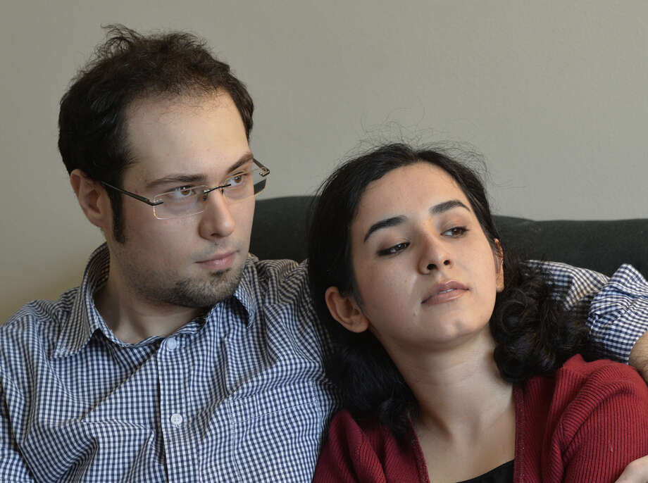 Danyal Mohammadzadeh holds his wife Maryam Mohammadzadeh in his arms at their home Wednesday afternoon Feb. 19, 2014 in Albany, N.Y.  The couple was caught up in the Wikileaks information exposure and their future return to their homeland in Iran is unsure.      (Skip Dickstein / Times Union) Photo: Skip Dickstein