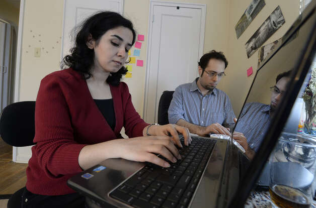 Danyal Mohammadzadeh and his wife Maryam Mohammadzadeh work on their computers at their home Wednesday afternoon Feb. 19, 2014 in Albany, N.Y.  The couple was caught up in the Wikileaks information exposure and their future return to their homeland in Iran is unsure.      (Skip Dickstein / Times Union) Photo: Skip Dickstein