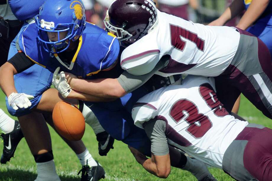 The pops out as Queensbury's Jared Bruno, left, gets tackled by Burnt Hills' John Whitney, top right, and Ricky Rodriguez during their football game on Saturday, Sept. 26, 2015, at Queensbury High in Queensbury, N.Y. (Cindy Schultz / Times Union) Photo: Cindy Schultz / 10033493A