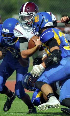 Burnt Hills' quarterback John Clayton, center, gets sandwiched by Queensbury's Joe Gerardi, left, and Brett Rodriguez during their football game on Saturday, Sept. 26, 2015, at Queensbury High in Queensbury, N.Y. (Cindy Schultz / Times Union) Photo: Cindy Schultz / 10033493A