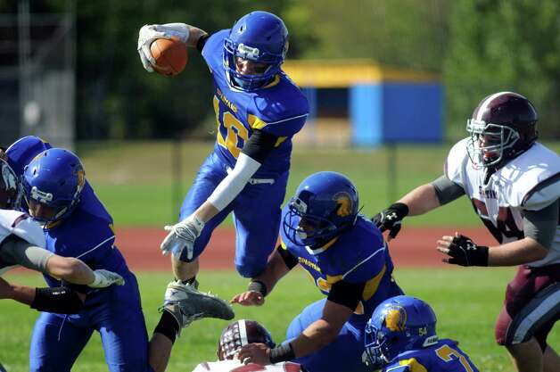 Queensbury's quarterback Kevin Collins, center, leaps over Burnt Hills' defense during their football game on Saturday, Sept. 26, 2015, at Queensbury High in Queensbury, N.Y. (Cindy Schultz / Times Union) Photo: Cindy Schultz / 10033493A