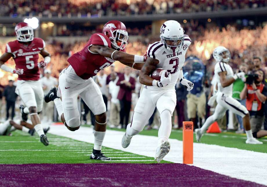 Texas A&M's Christian Kirk (3) is pushed out of the end zone after crossing the goal line for a touchdown, by Arkansas' Santos Ramirez (9), during the first half of an NCAA college football game Saturday, Sept. 26, 2015, in Arlington, Texas. (Sam Craft/The Bryan-College Station Eagle via AP) Photo: Sam Craft, Associated Press / The Bryan-College Station Eagle