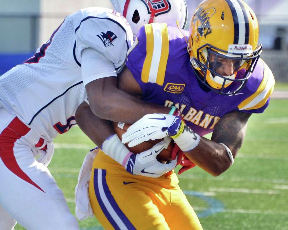 UAlbany's #1 Zee Roberson, right, is tackled by Duquesne's #10 Malik Shegog after a pass completion during Saturday's game at Bob Ford Field Sept. 26, 2015 in Albany, NY.  (John Carl D'Annibale / Times Union) Photo: John Carl D'Annibale / 00033508A