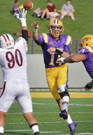 UAlbany QB DJ Crook, center, gets a pass off as Duquesne's #90 Dane O'cDriscoll, left, closes in during Saturday's game at Bob Ford Field Sept. 26, 2015 in Albany, NY.  (John Carl D'Annibale / Times Union) Photo: John Carl D'Annibale / 00033508A