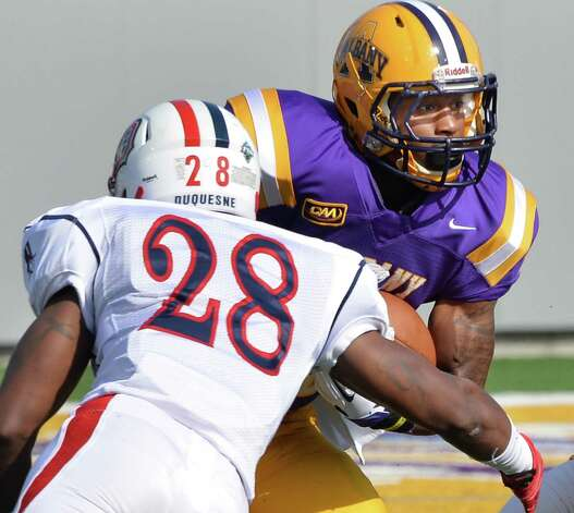 UAlbany's #35 Dione Alston, right, tries to get past Duquesne's #28 Troy Gethers during Saturday's game at Bob Ford Field Sept. 26, 2015 in Albany, NY.  (John Carl D'Annibale / Times Union) Photo: John Carl D'Annibale / 00033508A