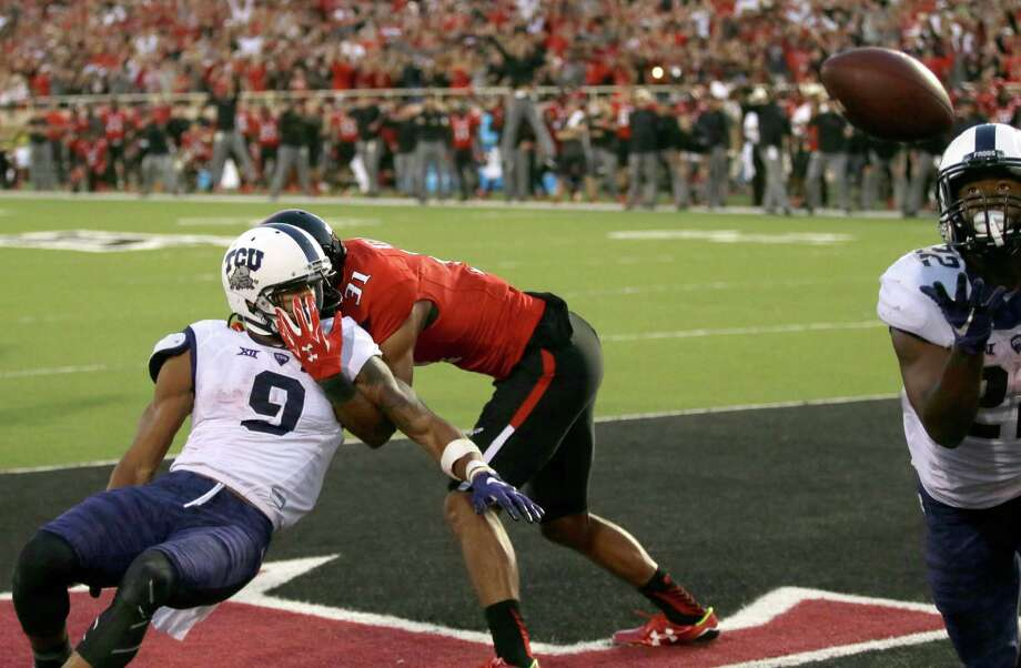 Texas Tech's Justis Nelson grabs TCU's Josh Doctson, left, the intended receiver, but Aaron Green, right, collects the tipped ball for the winning touchdown with 23 seconds left in the game Saturday. Photo: LM Otero, STF / AP
