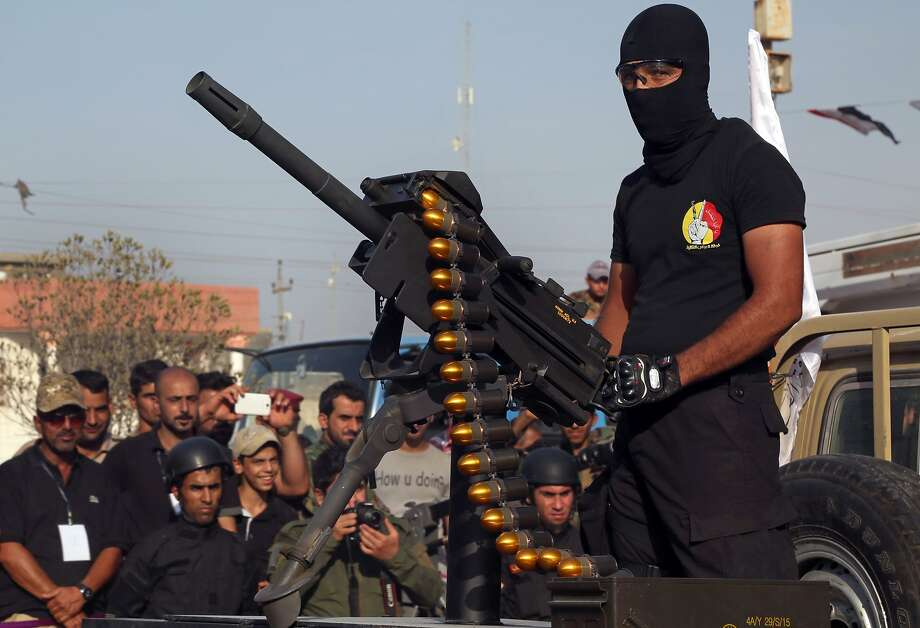 A member of the Abbas squad, a Shiite militia group, participates in a military parade Saturday in Basra, Iraq. Militias are training with government forces. Photo: Nabil Al-Jurani, Associated Press