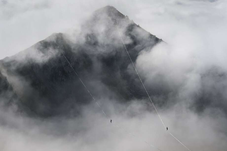 Two athetes compete in the fog during the Highline Extreme event in Moleson peakduring the Highline Extreme event in Moleson peak, western Switzerland on September 26, 2015. Fifty of the European best slackliners compete until September 27, 2015 on six different lines ranging from 45 metres to 495 metres. Photo: Fabrice Coffrini, AFP / Getty Images