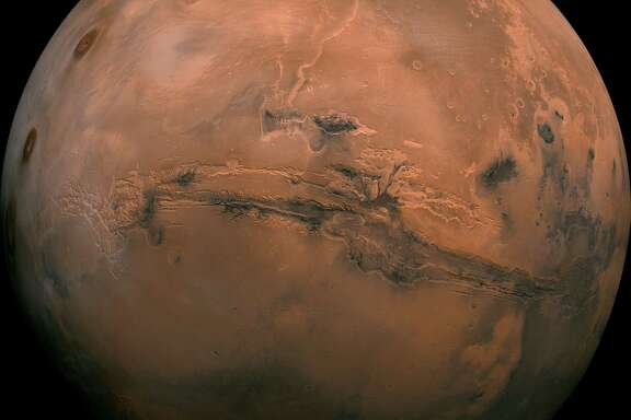 Mosaic of the Valles Marineris hemisphere of Mars projected into point perspective, a view similar to that which one would see from a spacecraft. The distance is 2500 kilometers from the surface of the planet, with the scale being .6km/pixel. The mosaic is composed of 102 Viking Orbiter images of Mars. The center of the scene (lat -8, long 78) shows the entire Valles Marineris canyon system, over 2000 kilometers long and up to 8 kilometers deep, extending form Noctis Labyrinthus, the arcuate system of graben to the west, to the chaotic terrain to the east. Many huge ancient river channels begin from the chaotic terrain from north-central canyons and run north. The three Tharsis volcanoes (dark red spots), each about 25 kilometers high, are visible to the west. South of Valles Marineris is very ancient terrain covered by many impact craters.