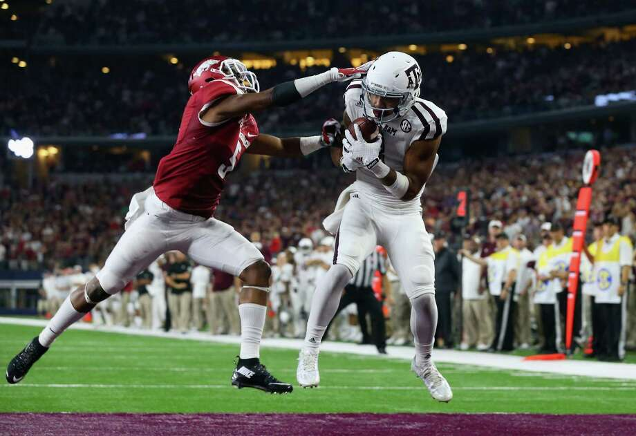 Texas A&M's Christian Kirk, right, beats Arkansas' Henre' Toliver to score the decisive touchdown in overtime in Saturday night's Southeastern Conference matchup at AT&T Stadium in Arlington. Photo: Ronald Martinez, Staff / 2015 Getty Images
