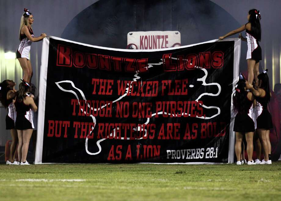 Kountze Lion's cheerleaders hold up a banner Friday Night at the Lion's Stadium. It has a verse from